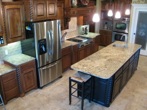 Kitchen with island and stainless steel refrigerator